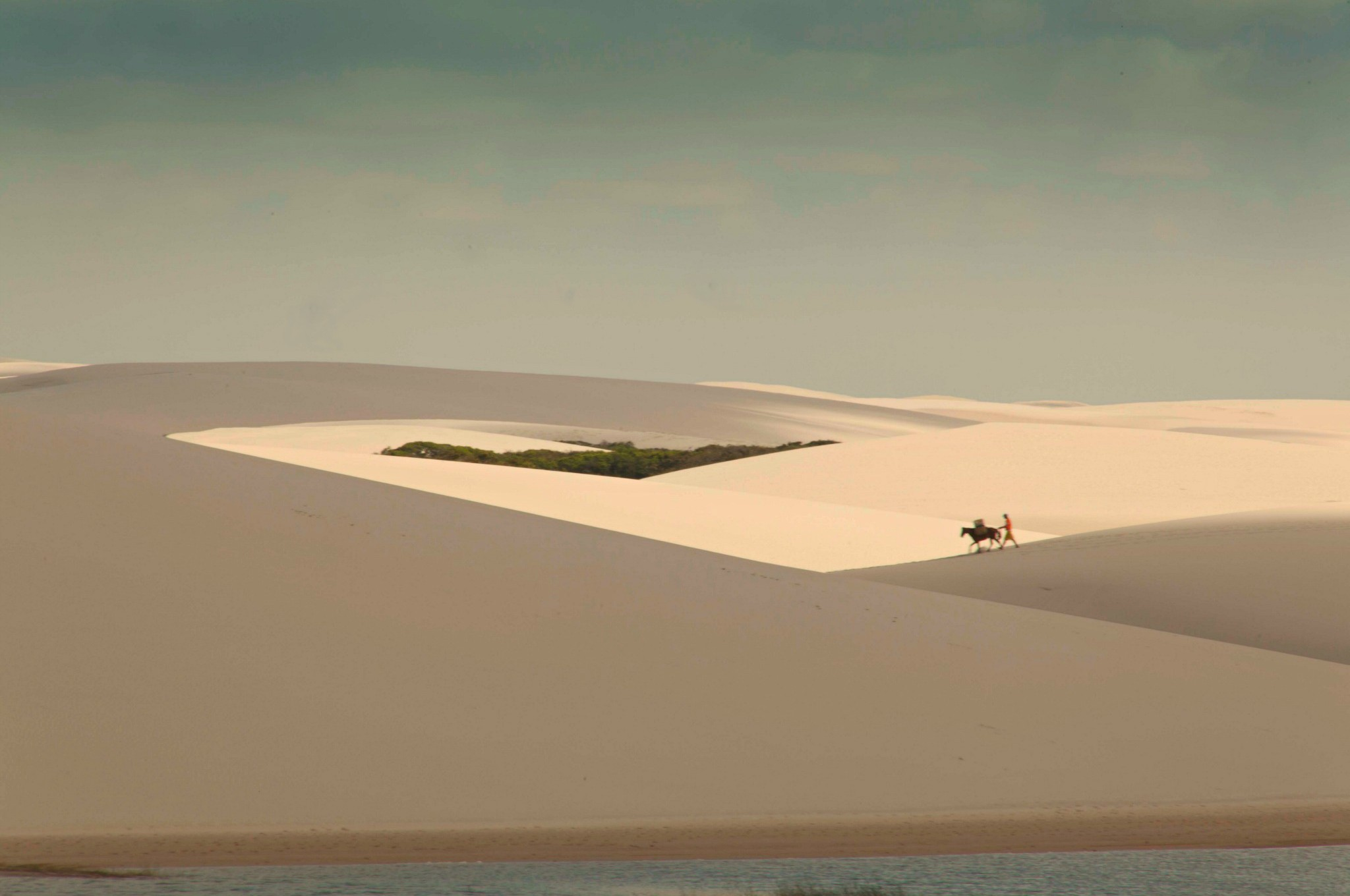 A men and his horse walking over dunes. Photo by Francois